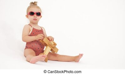 Baby wearing sunglasses plays with generic wooden toy plane
