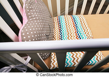 Baby white crib with a cute brown pink pillow with a can. brown mattress. Cozy bed for the baby