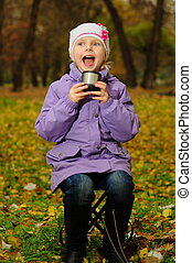 baby with a cup in the autumn park