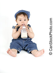 Baby with a milk bottle - Baby in denim outfit holding a...