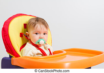 Baby with a pacifier at home