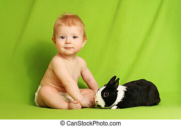 Baby with a rabbit sitting on a green blanket.