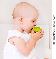 baby with an apple - cute baby girl eating a green apple in...