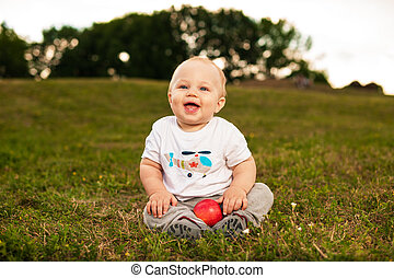 Baby with apple outdoors - Smiling beautiful baby looking at...
