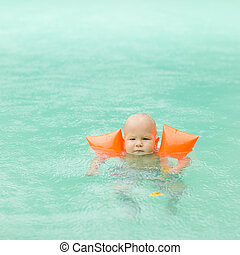 Baby with armbands in swimming pool