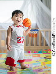Baby with ball in basketball uniform
