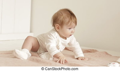 baby with beautiful blue eyes lying on her bed at home. Cute Little Girl is Looking Into The Camera