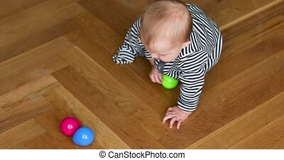 Baby with big blue eyes plays with colorful toys
