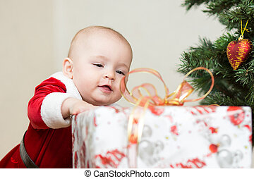 baby with big gift box on christmas tree background