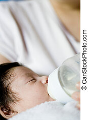 baby with bottle - a baby drinking a bottle of formual in...