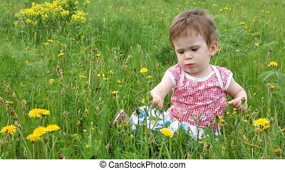 Baby with dandelions on green spring lawn