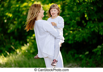 Baby with down sydrome enjoying outdoor play