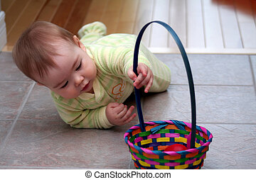 Baby with Easter Basket - a baby boy in pajamas crawling to...