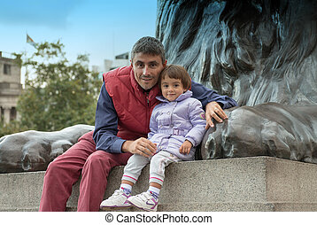Baby with father playing at the base of Nelson Column in Trafalgar Square - London