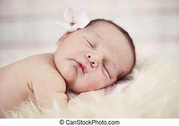 Baby with flower sleeping on fur