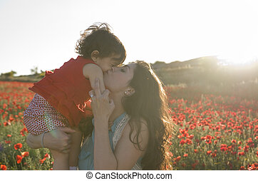baby with his mother enjoying a field day outdoors, kissed in sunset backlight