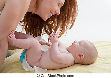 Baby with mother diapering and playing smiling having fun
