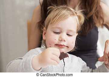 baby with mother eating chocolate