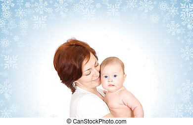 Baby with mother on snowy background