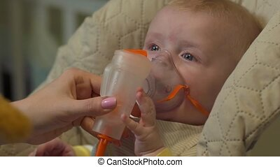 Baby With Oxygen Mask - Baby with oxygen mask sitting in...