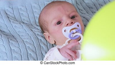 Baby with pacifier - On the bed lies an infant with a...