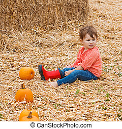 Baby with pumpkins on a farm