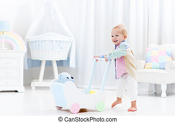 Baby with push walker in white bedroom