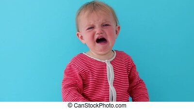 Baby with red face crying loudly - Little toddler in striped...