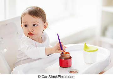 baby with spoon eating puree from jar at home - food, child,...