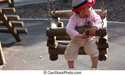 Baby with Sun Hat in Swing