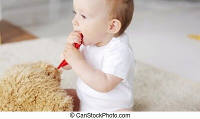 baby with teddy bear sitting on floor at home 27
