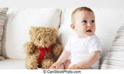 baby with teddy bear sitting on sofa at home