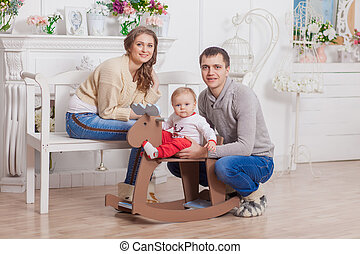 Baby wooden horse swing near christmas decorated tree with parents