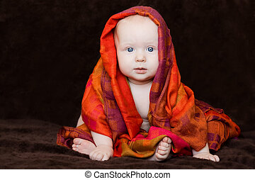 Baby wrapped in red orange scarf
