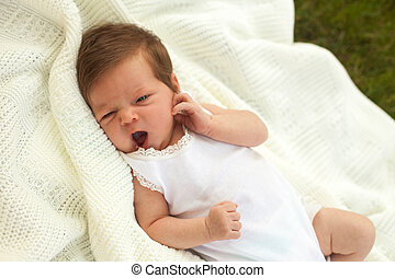 Baby yawing on the blanket on the grass