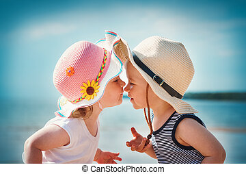 Babygirl and babyboy kissing on the beach