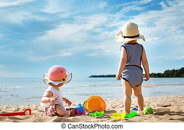 Babygirl and babyboy on the beach