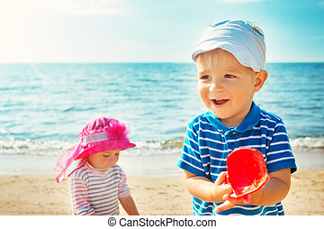 Babygirl and babyboy playing on the beach
