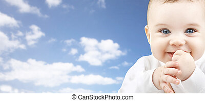 happy baby face over blue sky background