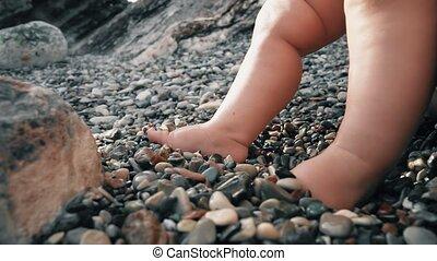 Baby's bare feet on pebble beach, close-up shot - Baby's...