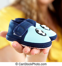 baby's bootee on a palm of future mum