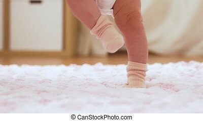 babyhood and people concept - baby's feet in socks stepping on knitted plush blanket