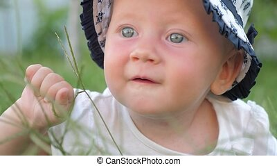 Baby girl with blue eyes is touching green grass during sunny summer day background