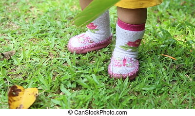 baby's legs walking on the grass