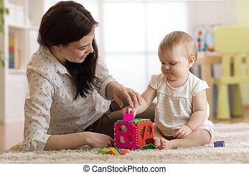 Babysitter and baby playing with toys in nursery