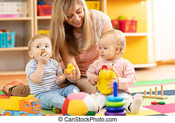 babysitter and children play together in nursery or at home