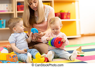 babysitter and children play together in nursery or day care centre