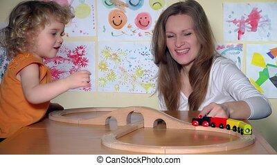 babysitter, en, nieuwsgierig, toddler, meisje, spel met, houten speelgoed, trein, in, kleuterschool