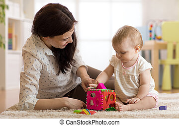 Babysitter looking after baby. Child plays with sorter toy sitting on the carpet at home