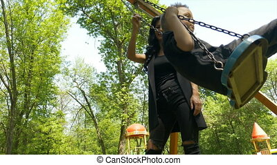 Babysitter pushing baby boy on swing set and enjoying a sunny day in the park